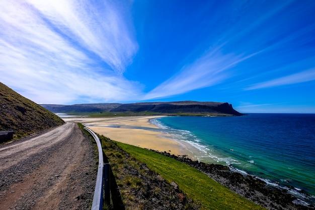 Onverharde weg in de buurt van een met gras begroeide heuvel en de zee met een berg in de verte onder een blauwe hemel