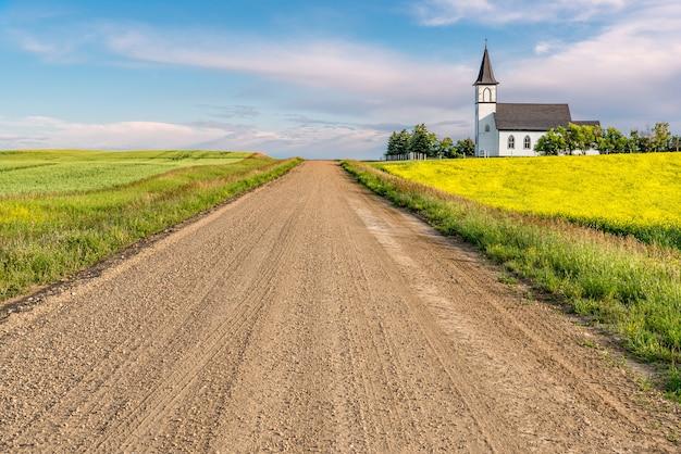 Onverharde weg in het land die leidt naar de historische, maar verlaten grand valley lutheran church nabij willow bunch, sk