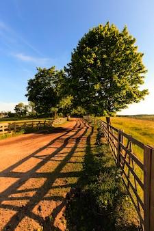 Onverharde weg in het landelijke gebied van de boerderij. omsloten door een houten hek