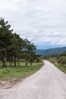 Onverharde weg langs de heuvel met het verkeersteken.