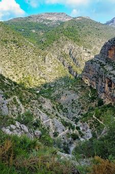 Onverharde weg met trappen die de berg afbuigen voor wandelaars.