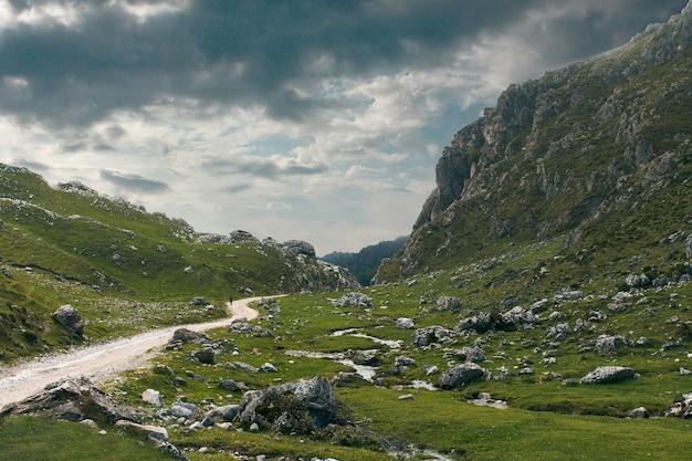 Onverharde weg omringd door met gras bedekte landen en bergen op een bewolkte dag