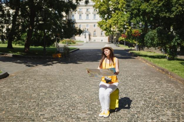 Onverschillige reiziger toeristische vrouw in gele kleding, hoed zittend op koffer kijkend op stadskaart zoekroute buiten. meisje dat naar het buitenland reist om een weekendje weg te reizen. toeristische reis levensstijl.