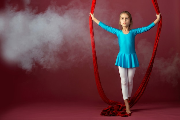 Onverschrokken mooi klein meisje in een blauw gymnastiekpak toont een stunt luchtfoto rood lint omgeven door rook op een schelle bleke achtergrond. concept van geavanceerde acrobaten gymnasten