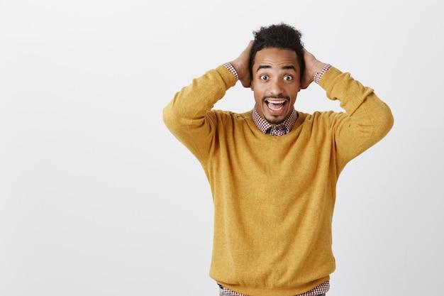 Onverwacht goed nieuws maakt de dag stralend. verbaasde knappe afrikaanse man in casual gele trui hand in hand op het hoofd van ongeloof, blij zijn na een positieve gebeurtenis, staande over grijze muur
