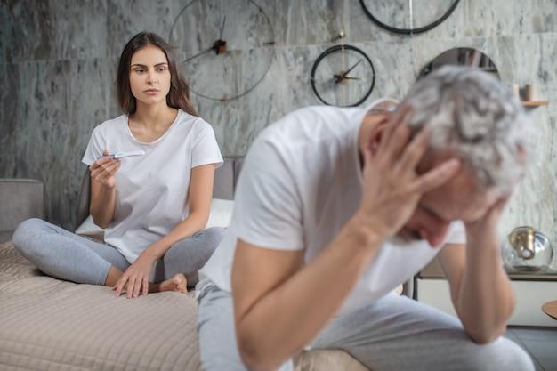 Onverwacht nieuws. triest langharige vrouw zittend op bed met zwangerschapstest en verbaasde man met handen gevouwen zijn hoofd