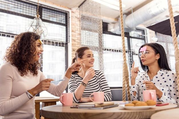 Onverwachte beweging. vrolijke drie vrienden die spel dirigeren terwijl ze in café poseren en lachen