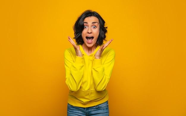 Onverwachte overwinning. opgewonden en gelukkig brunette meisje gekleed in een gele hoodie, onverwachte overwinning vieren met haar handpalmen geopend.