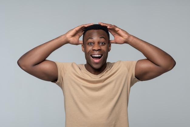 Onverwachte vreugde. blije verrast jonge volwassen donkere man in lichte t-shirt die gespierde armen opheft naar zijn hoofd