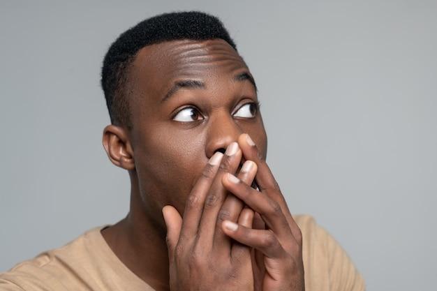 Onverwachte wending. jonge volwassen verrast donkerhuidige man met wijd open ogen die naar kant kijken die zijn mond met handpalmen bedekken