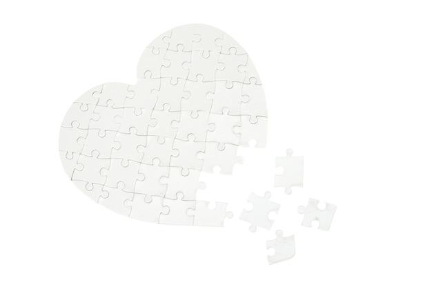 Onvolledige puzzel in een vorm van een hart dat op wit wordt geïsoleerd