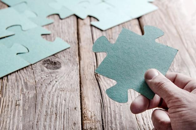 Onvolledige puzzels liggend op houten rustieke planken en hand met puzzelstukje