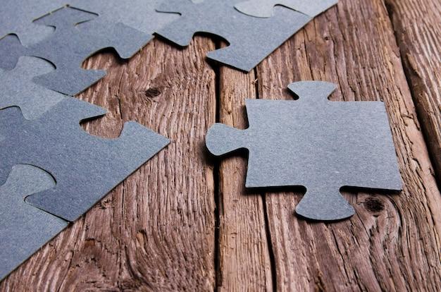 Onvolledige puzzels liggend op houten rustieke planken.