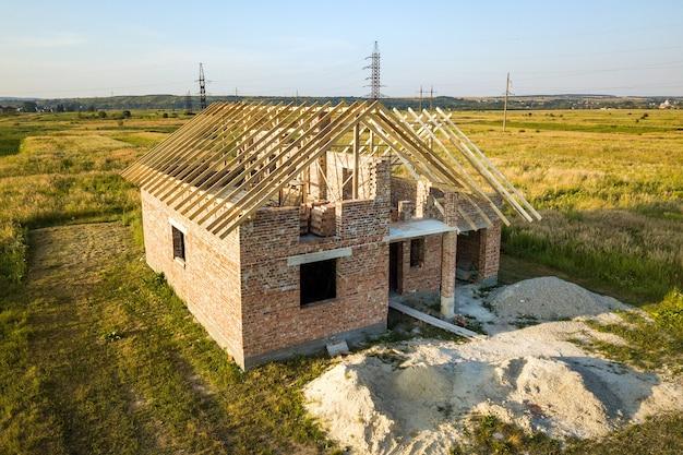 Onvoltooid bakstenen huis met houten dakconstructie in aanbouw.
