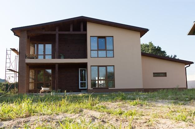 Onvoltooide architecturale bruin onroerend goed gebouw ontwerp op grasachtig landschap.