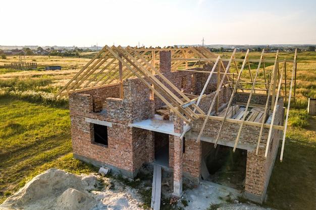 Onvoltooide bakstenen huis met houten dakconstructie in aanbouw.