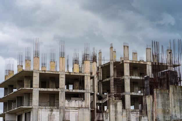 Onvoltooide bouw bouwplaats werknemers tegen bewolkte hemelachtergrond