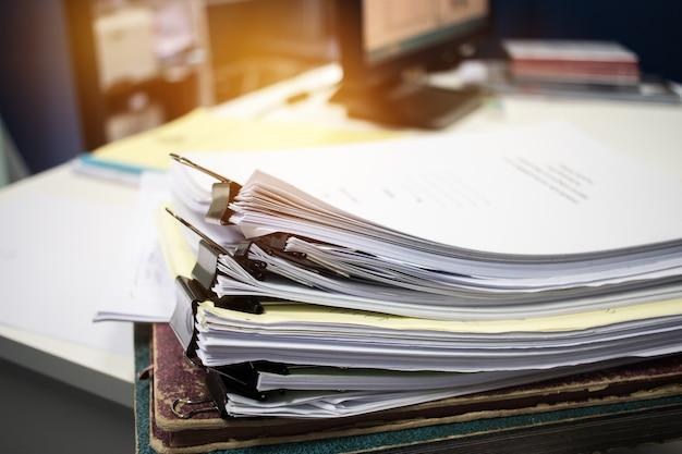 Onvoltooide documenten stapels papieren bestanden op bureau voor rapportdocumenten, stapels van onafgewerkte papieren blad bereikt met clips indoor, business offices concept. document wordt geschreven, getekend en gepresenteerd.
