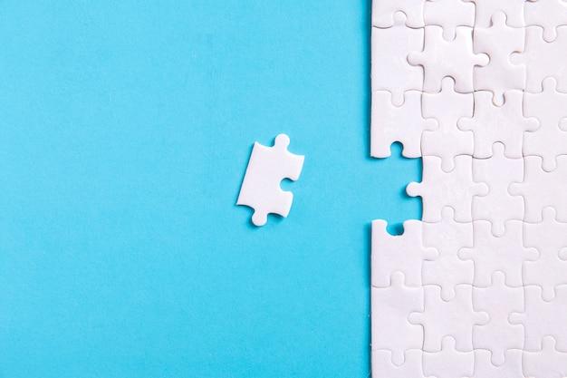 Onvoltooide puzzel op blauw met kopie ruimte voor uw tekst of inhoud