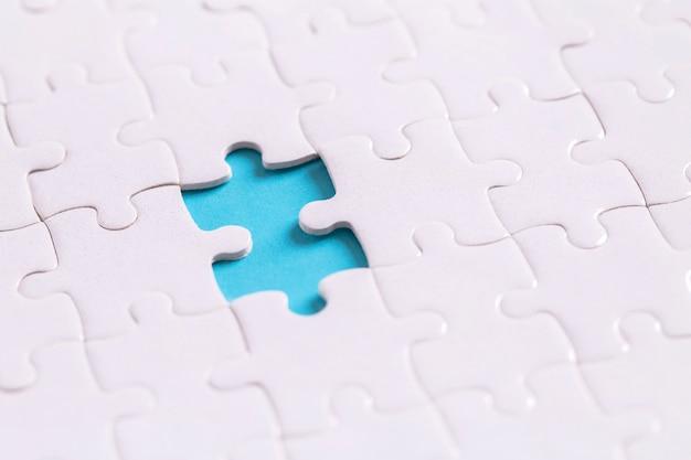Onvoltooide puzzel op blauw met kopie ruimte