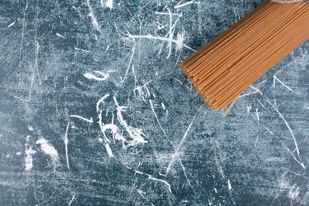 Onvoorbereide deegwarenbos van volkoren spaghetti vastgebonden met touw op marmeren backgroundto