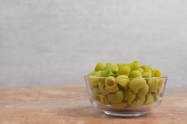 Onvoorbereide groene macaroni in glasplaat op marmeren achtergrond. hoge kwaliteit foto