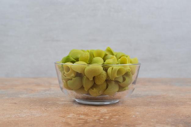 Onvoorbereide groene macaroni in glasplaat op marmeren ruimte.