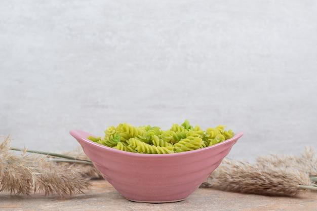 Onvoorbereide groene spiraalvormige pasta op roze kom.