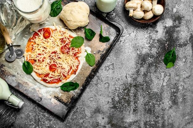 Onvoorbereide pizza met ingrediënten op rustieke tafel.