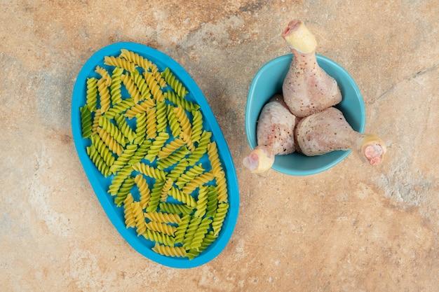 Onvoorbereide spiraalvormige macaroni met kippenpoten op blauw bord.