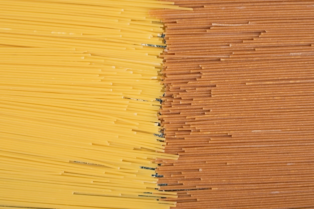Onvoorbereide verse bruine en gele pasta op marmeren achtergrond. hoge kwaliteit foto