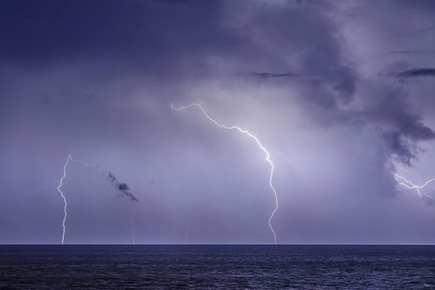 Onweer boven de zee, bliksem slaat op het water