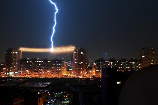 Onweer in de stad, bliksem insloeg in de hoogspanningslijn tussen het huis