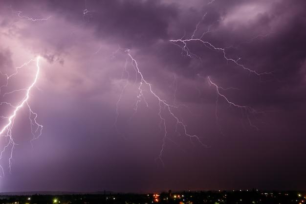 Onweersbui met bliksem aan de hemel boven een klein stadje