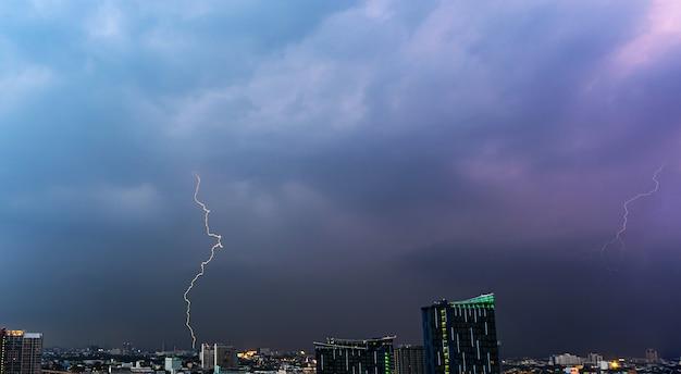 Onweersbuibliksem over de stad bij zonsondergang