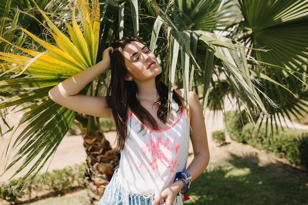Onweerstaanbaar meisje met donker steil haar rusten in de schaduw van palmbomen genieten van vakantie in exotisch land. portret van schattige jonge vrouw poseren met ogen gesloten met zuidelijke planten