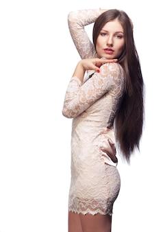 Onweerstaanbare vrouw in kanten jurk kijkt over haar schouder en raakt haar lange haren geïsoleerd op wit aan