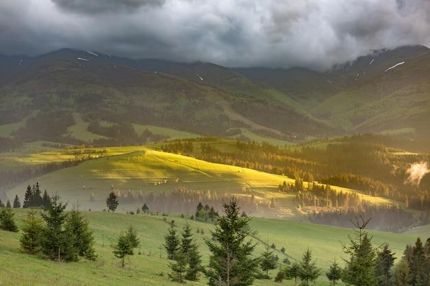 Onweerswolken over de bergen en groene weiden tijdens zonsondergang
