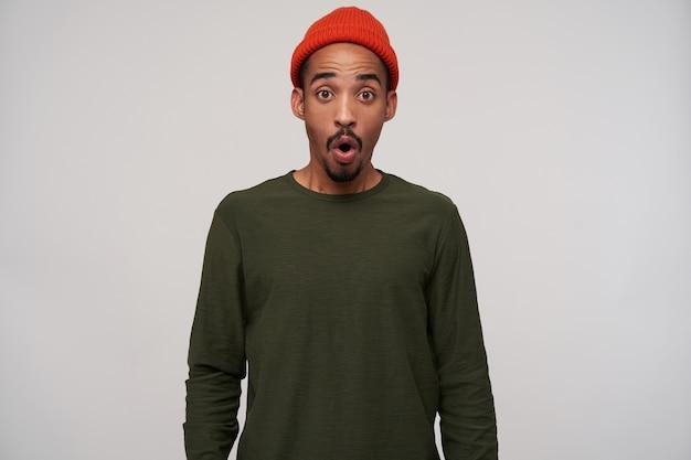 Onweldige jonge bebaarde brunette man met donkere huid kijkt verbaasd met ronde ogen, draagt rode hoed en kaki trui op wit