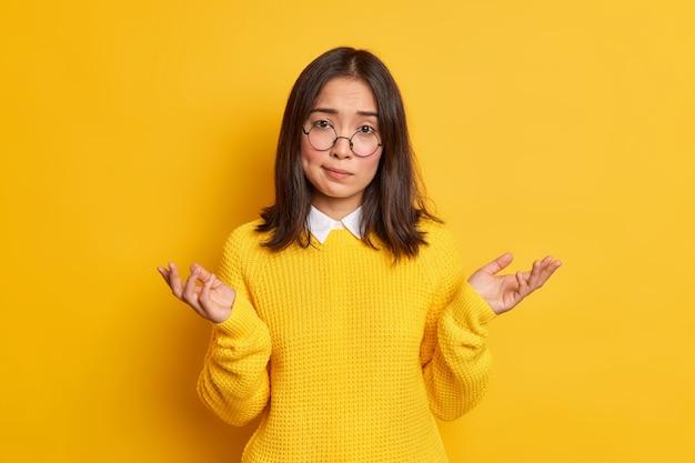 Onwetende aarzelende aziatische vrouw haalt schouders op in een onnozel gebaar en kan geen beslissing nemen, draagt een ronde bril en een losse trui.