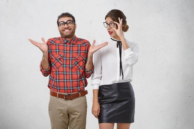 Onwetende, onhandige man draagt een geruit overhemd en een bril met dikke lenzen, haalt verbijsterd zijn schouders op