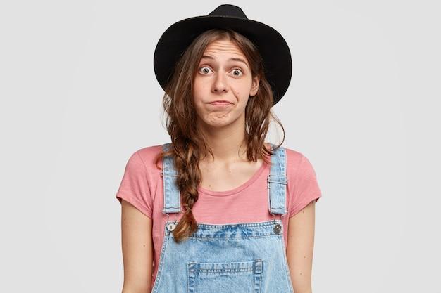 Onwetende, verbaasde aarzelende vrouw draagt modieuze outfit, kijkt verbijsterd, schaamt zich terwijl ze een keuze maakt