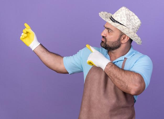 Onwetende volwassen mannelijke tuinman die een tuinhoed en handschoenen draagt, kijkend en wijzend naar de zijkant geïsoleerd op een paarse muur