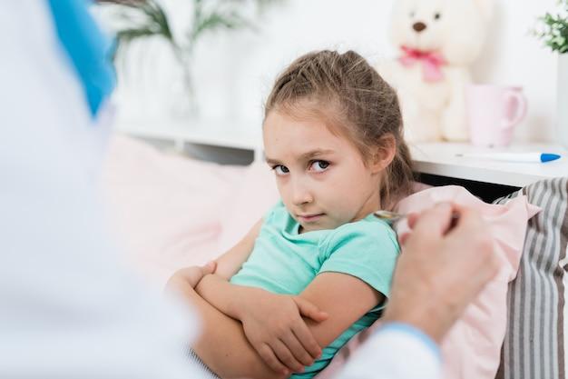Onwillig ziek meisje kijken naar lepel met medicijnen gehouden door arts zittend in bed thuis