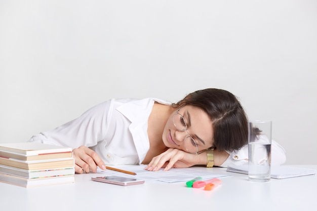 Onworked brunette student leunt op handen op bureau, dutje op de werkplek, voelt vermoeidheid, draagt een wit overhemd, poseert op wit. mensen, zaken en vermoeidheid concept. vermoeide persoon binnen