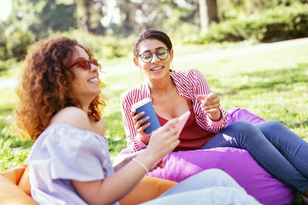 Onze dag samen. uitbundige donkerharige vrouw die koffie drinkt en met haar vriend in de open lucht ontspant