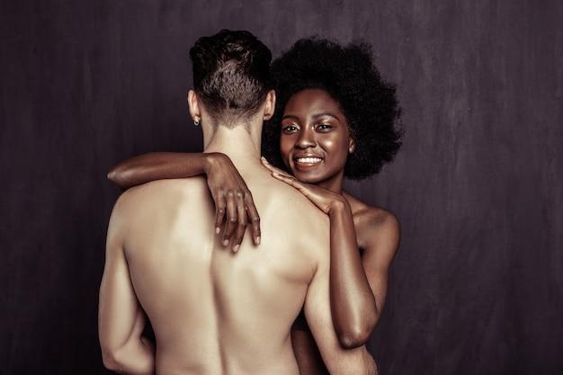 Onze lichamen. vrolijke naakte vrouw die lacht terwijl ze haar geliefde vriendje knuffelt
