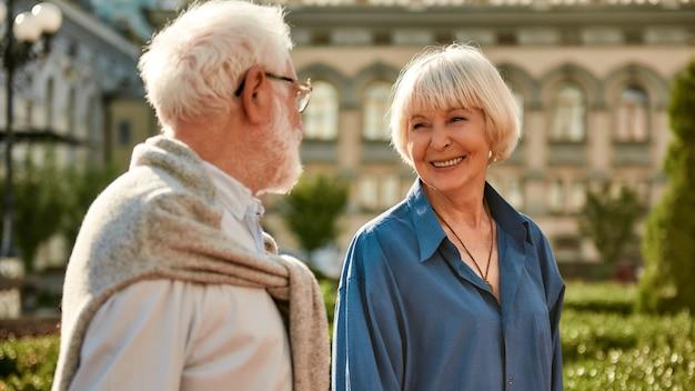 Onze liefde verandert niets aan een mooi senior stel dat elkaar met een glimlach aankijkt terwijl ze geld uitgeven