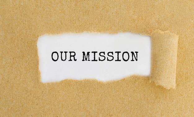 Onze missie verschijnt achter gescheurd bruin papier.