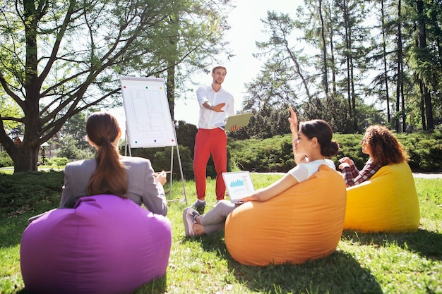 Onze studies. geïnspireerde jongeman die in de buurt van het bord staat en hun universitaire project met zijn vrienden bespreekt